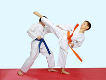 Blows karate are training athletes on a bright and red background Royalty Free Stock Images