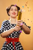 Blows up cracker. Happy girl on yellow background blows up cracker, colorful confetti slowly scatter and fall Stock Photos