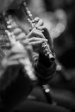 Blåsa flöjt i händerna av en musiker i orkestercloseupen Royaltyfri Bild