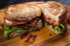 Bacon lettuce and tomato sandwich. BLT sandwich with fried bacon, lettuce and tomato in slices of bread Stock Photos