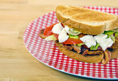 BLT sandwich on gingham plate Stock Photo
