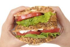 BLT sandwich by holding hands Royalty Free Stock Photos