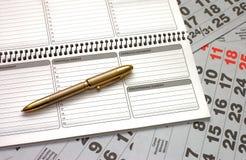 Blätter eines Kalenders und des Notizbuches Stockbild