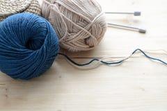 Blu e beige che tricottano le bugne del filato sulla tavola di legno Immagine Stock Libera da Diritti