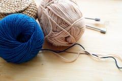 Blu e beige che tricottano le bugne del filato sulla tavola di legno Immagini Stock Libere da Diritti
