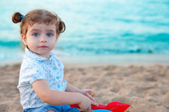Blu eyes brunette toddler girl playing with sand in beach. At mediterranean royalty free stock photo