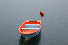 Blu and orange boat on the lake. A blu and orange boat on the lake under the rain Stock Photo