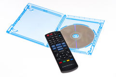 Blu-ray disc with remote control. The picture shows a blu-ray disc with a remote control to show a scene of watching a movie Stock Photography