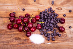 Bluberry cherry and sugar on old wooden background Stock Image