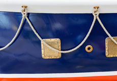 Blue aboard an old ship and hanging on the rope it in bronze eyelets Royalty Free Stock Photos