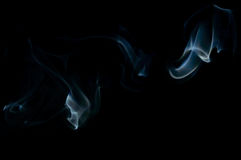 Blue abstract smoke art plume going from left to right. On a black background Royalty Free Stock Image