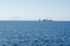 Blue aegean sea. Oil platform. Petrol Energy. Coast of The Greek island Thassos. Blue aegean sea and the main land in far distance. Oil platform Royalty Free Stock Photo