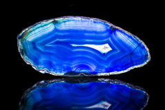 Blue agate slice, black background, healing stone and mineral Royalty Free Stock Photo
