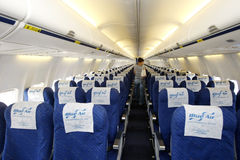Blue Air airplane interior. A passenger enters to an empty Blue Air airplane preparing for the takeoff Stock Photos