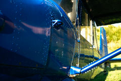 Blue airpane parked on the grass at the airfield Stock Image