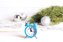 Blue alarm clock with Christmas decorations on white background. Christmas timer. Time to celebrate. Copy space Stock Image