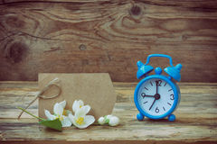 Blue alarm clock, empty paper tag, jasmine branch Stock Image