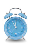 Blue alarm clock with the hands at 11 and 12 isolated on a white background Stock Images