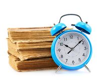 Blue alarm clock next to a stack of books Royalty Free Stock Photo