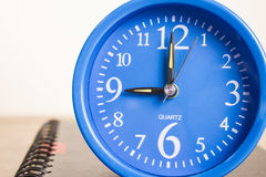 Blue alarm clock and notebook Royalty Free Stock Images