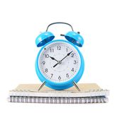 Blue alarm clock over the notebook Stock Photo