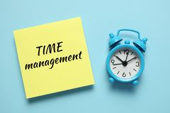 Blue alarm clock and paper reminder. Time management, priorities, efficiency, control and goals stock images