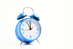 Blue alarm clock. Picture of a blue retro alarm clock on a white background with the clock five to twelve Royalty Free Stock Photography