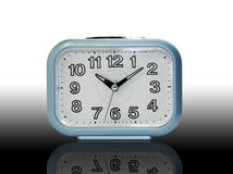 Blue alarm clock with shadow on black gradient background Royalty Free Stock Photos