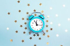 Blue alarm clock with small golden stars. royalty free stock photography