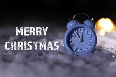 Blue alarm clock on snow and message MERRY CHRISTMAS against dark background. Winter holidays stock photo
