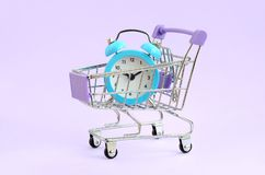 Blue alarm clock in supermarket trolley on violet background royalty free stock images