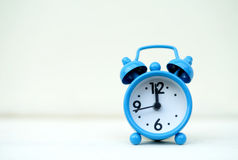 Blue alarm clock on white wall. Stock Image