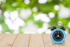 Blue alarm clock on wood texture Green bokeh Royalty Free Stock Photos