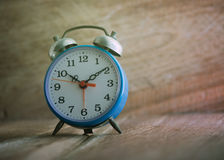 Blue alarm clock on wooden table Stock Image