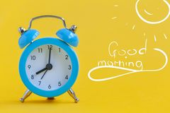 Blue alarm clock on yellow background with text Good morning. Minimalism. Contrast concept. Blue alarm clock on yellow background with text Good morning. Minimal royalty free stock photos