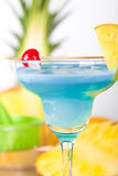 Blue alcohol cocktail with pineapple and cherry Stock Photos