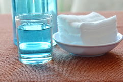 Blue alcohol for wash wound in glass and clean white cotton. On table Royalty Free Stock Image
