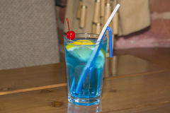 Blue alcoholic cocktail in the faceted glass. Stock Photos