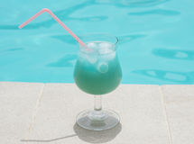 Blue alcoholic cocktail near clear pool water Royalty Free Stock Image