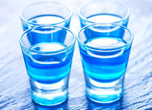 Blue alcoholic drink into small glasses Stock Photos