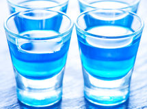 Blue alcoholic drink into small glasses Stock Images