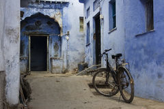 Blue Alleyway and Bicycle. A little blue alleyway that leads to an elaborate blue door.  There's a bicycle and an old time feel Stock Photos