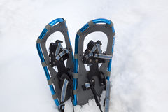 Blue aluminum snowshoes in a snowbank. A pair of blue aluminum snowshoes in a snowbank Royalty Free Stock Images