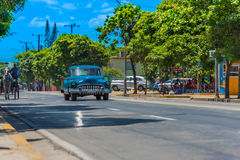 Blue american classic car drive on the road trough Varadero Cuba with carriage on the street side Stock Photo