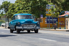 Blue american classic car drive on the road trough VaraderoCuba Stock Image