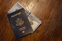 Blue American passport with some US dollars on top of a wooden desk. One blue American passport with some one hundred dollar bills on top of a wooden desk top Stock Image