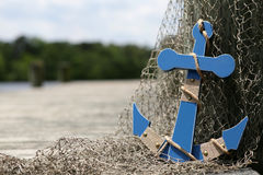 Blue anchor by the dock. Anchor in fishing net on old wooden pier stock images