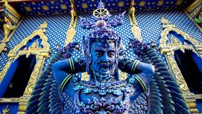 Blue angel in northern Thailand temple. With yellow Thai art as a background Royalty Free Stock Image