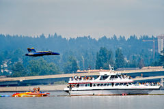 Blue Angels Seafair Vapor Trail. The Blue Angels Navy stunt performance plane flying over the log boom race crowd at Seafair Sunday on Lake Washington in seattle Royalty Free Stock Photos