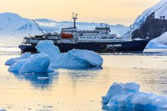 Blue antarctic cruise vessel among the icebergs with glacier in. Background, Neco bay, Antarctica Royalty Free Stock Photography
